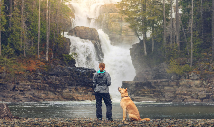 Full length of woman with dog by waterfall