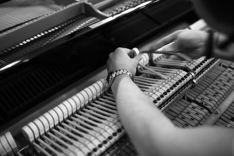 Close-Up Of Person Fixing Piano
