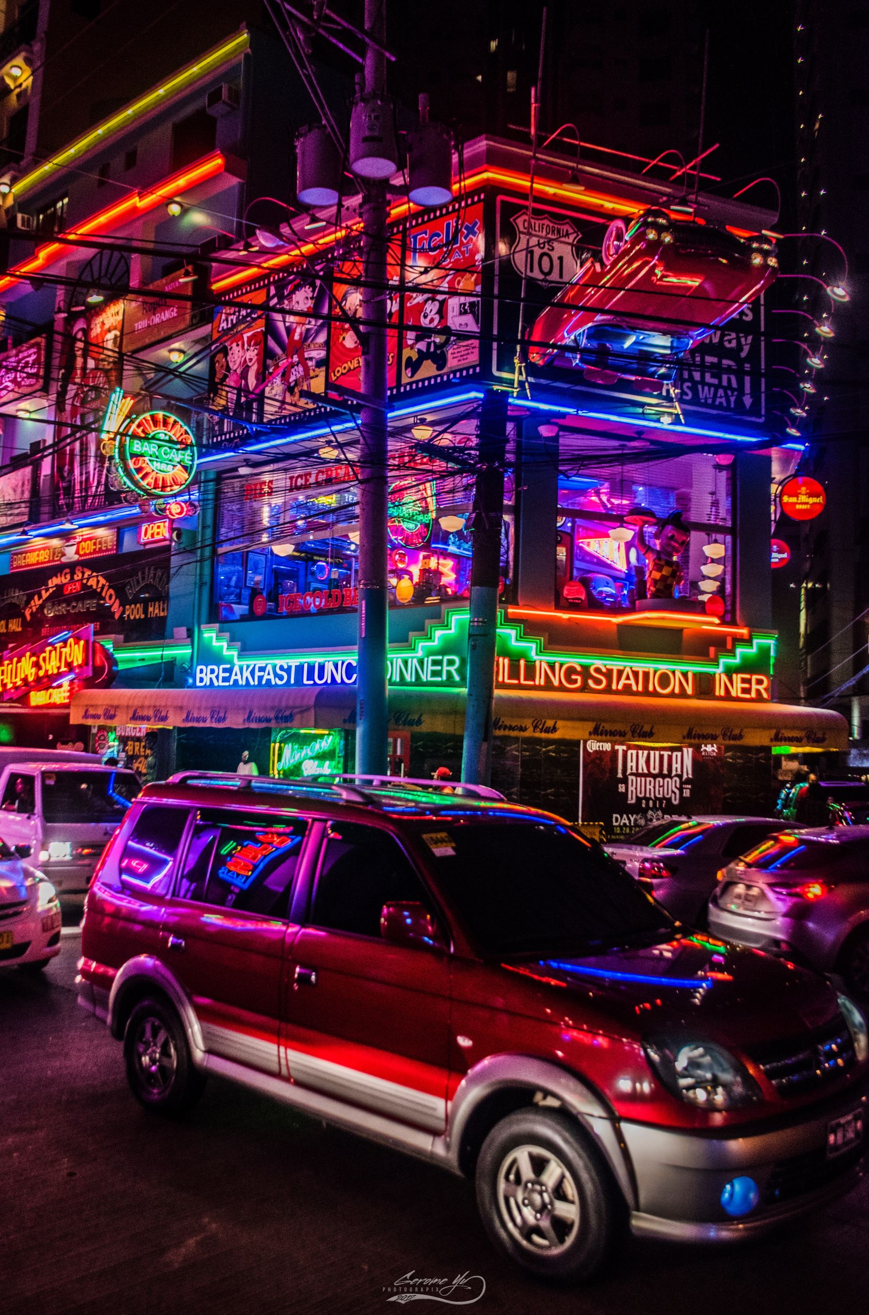 illuminated, car, night, mode of transportation, city, motor vehicle, transportation, neon, text, multi colored, architecture, communication, street, building exterior, no people, land vehicle, western script, built structure, motion, outdoors, nightlife