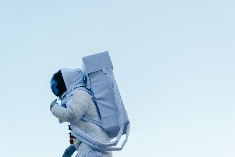 Person wearing astronaut costume while standing against white background