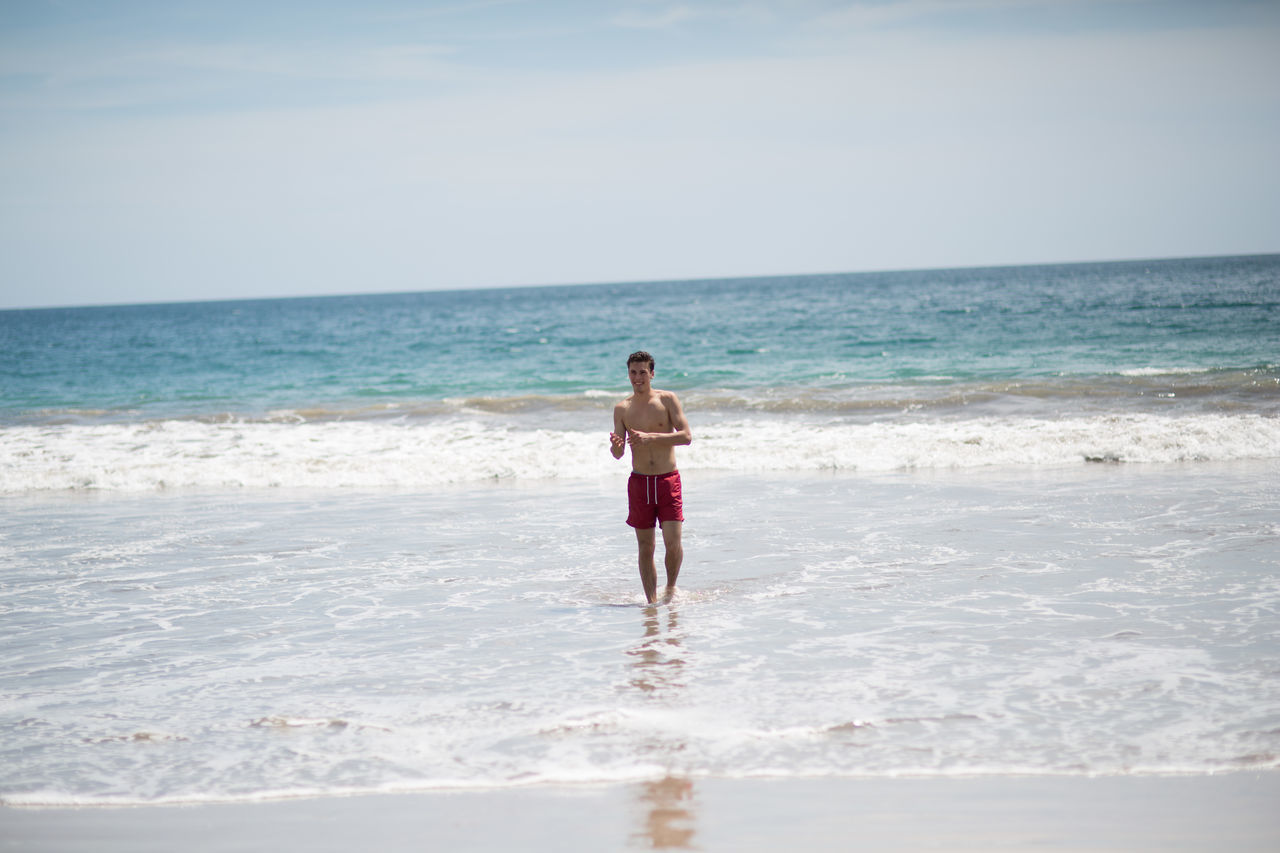 sea, horizon over water, beach, water, nature, one person, full length, standing, real people, sky, leisure activity, beauty in nature, scenics, rear view, walking, lifestyles, day, outdoors, shirtless, vacations, young adult, ankle deep in water, wave, young women, people