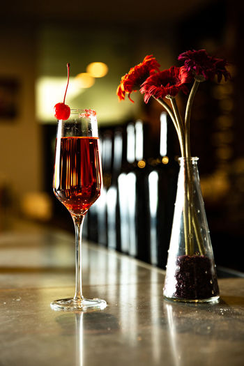 Glass Alcohol Food And Drink Drink Refreshment Freshness Flowering Plant Table Wineglass Red Flower Wine Vase Indoors  Glass - Material Close-up Focus On Foreground No People Plant Still Life Red Wine Bar Counter