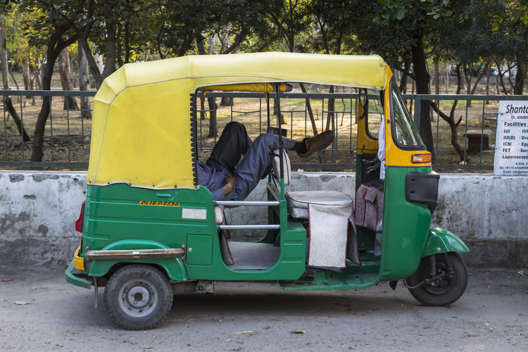 Low section of man resting in rickshaw against park