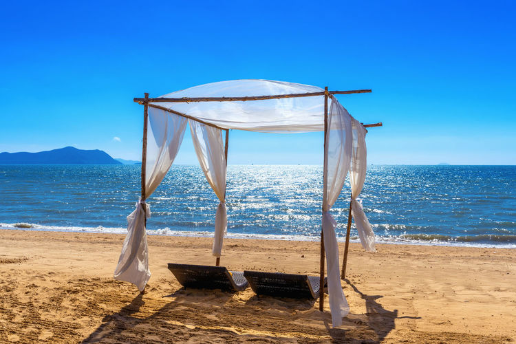 Beach canopies with sun loungers on beach. Sea Land Beach Water Sky Sand Horizon Over Water Horizon Scenics - Nature Blue Nature Beauty In Nature Tranquil Scene Sunlight Tranquility Day No People Idyllic Clear Sky Outdoors