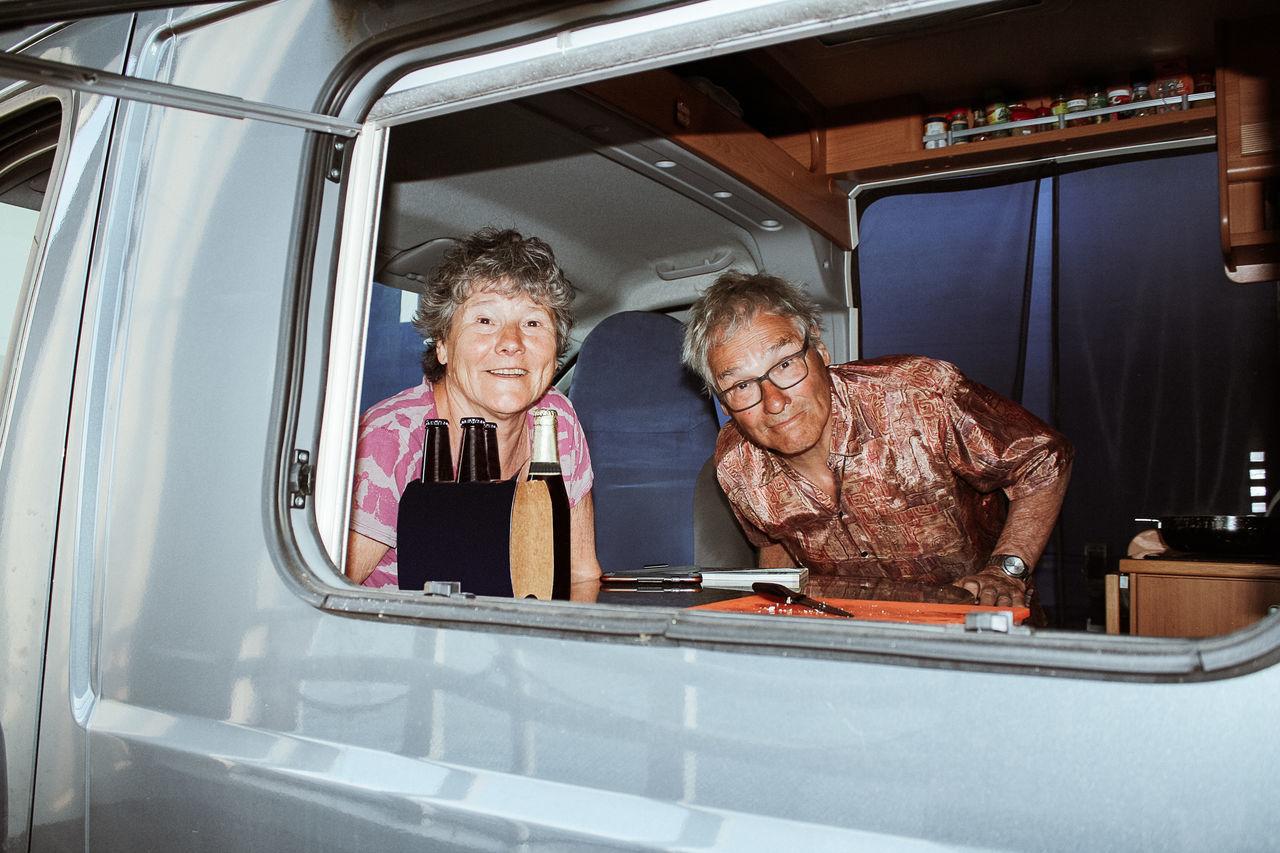 Portrait of senior couple in motor home seen through window