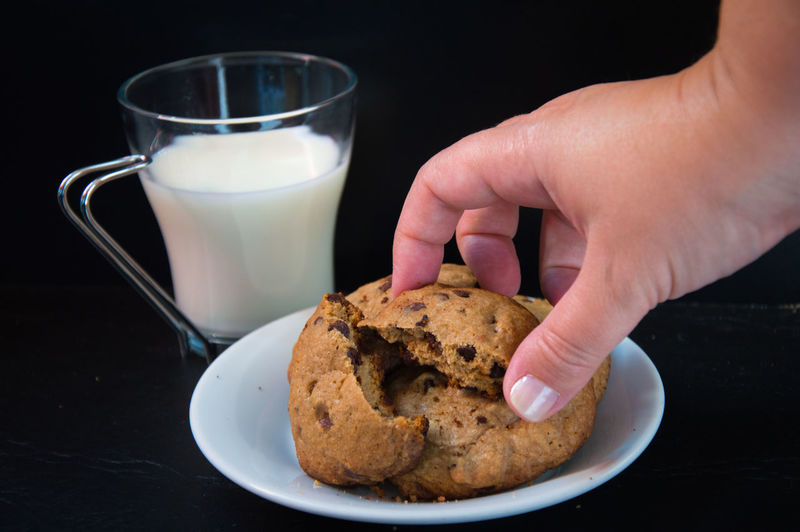 Cropped hand of woman holding cookie by milk glass