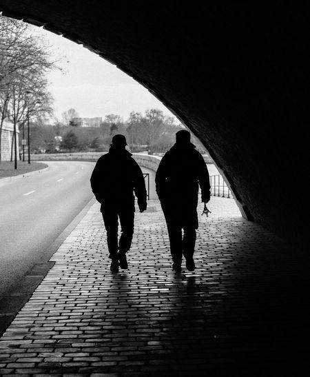 Rear view of silhouette men walking on road