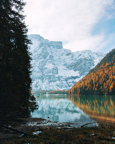Scenic view of lake by snowcapped mountains against sky in autumn, lake braies