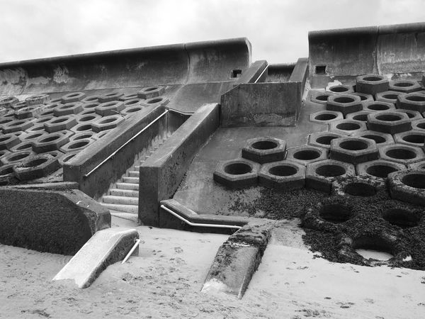 monochrome image of the seawall south of blackpool constructed of concrete honeycomb type structures with steps leading to the beach covered in tidal seaweed and dramatic grey sky Blackpool Concrete Sea Wall No People Nature Beach Coast Architecture Wall - Building Feature Built Structure Sky Day Outdoors Wall