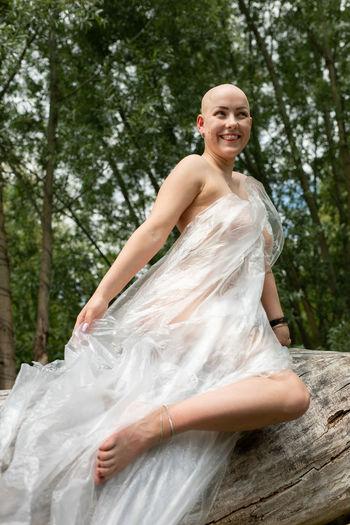 Smiling naked woman wearing polythene sitting on tree trunk