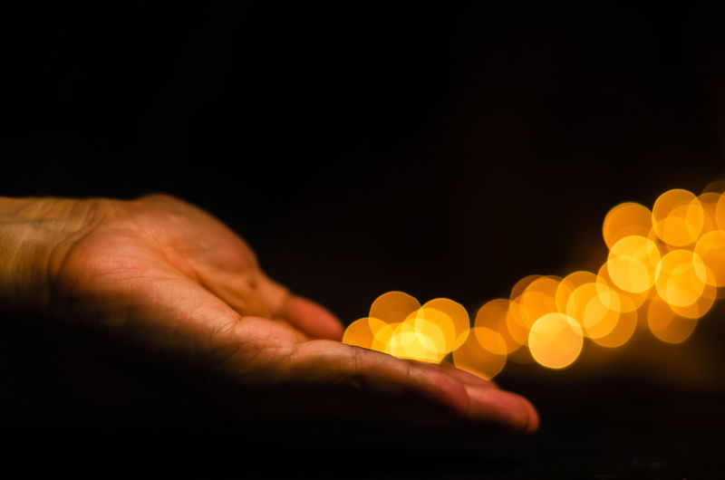 The hand releases yellow round shape bokeh light on black background.