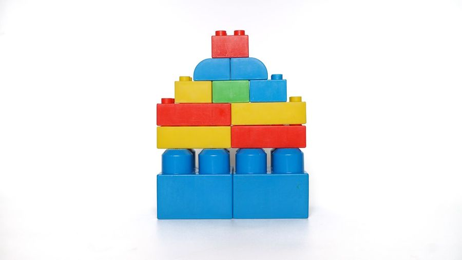 Stack of multi colored toy against white background