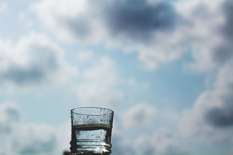 View of glass of water against cloudy sky