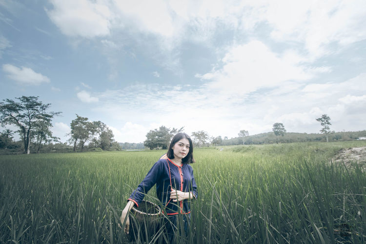 Young woman carrying basket while standing amidst crops on field against sky