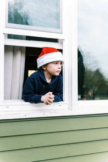 Portrait of a boy looking through window