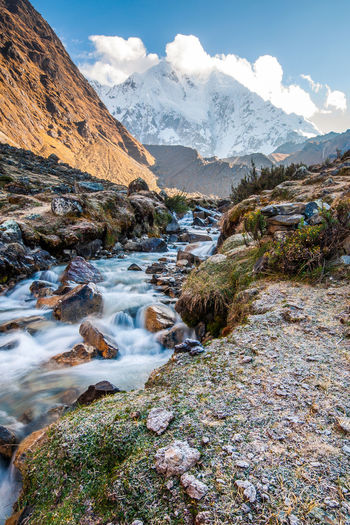 Scenic view of stream flowing by mountains