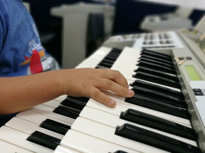 Close-Up Of Boy Playing Piano