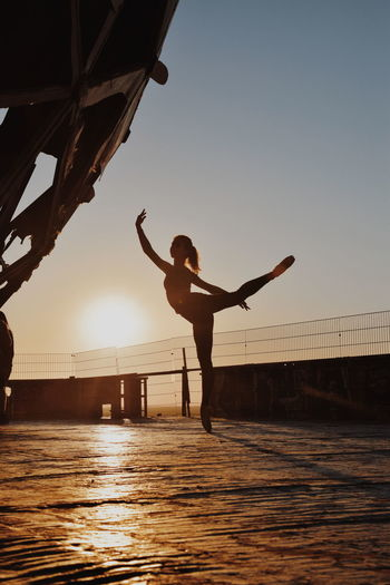 Silhouette teenage girl dancing against sky during sunset