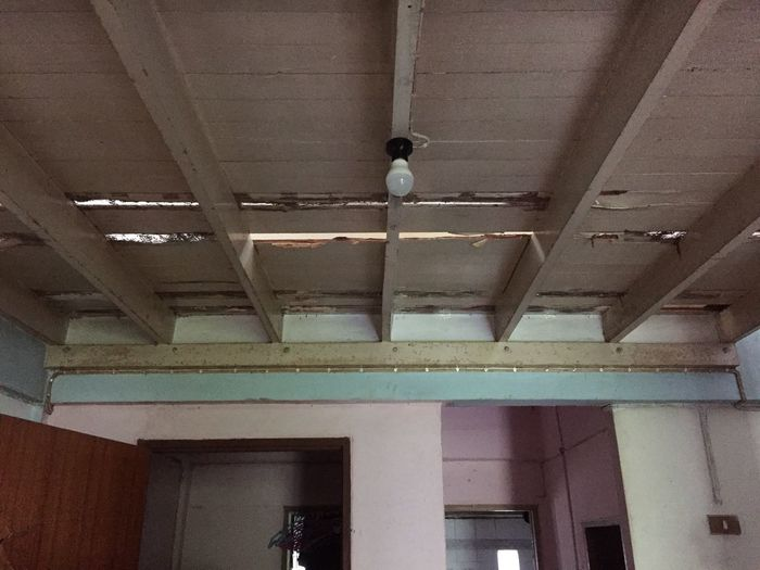 Low angle view of illuminated lights hanging on ceiling of building