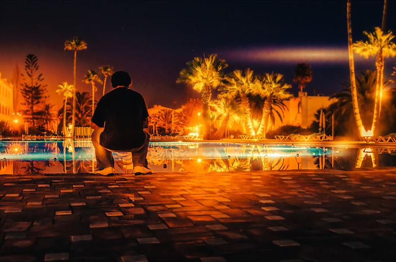 Rear view of man sitting on illuminated city at night