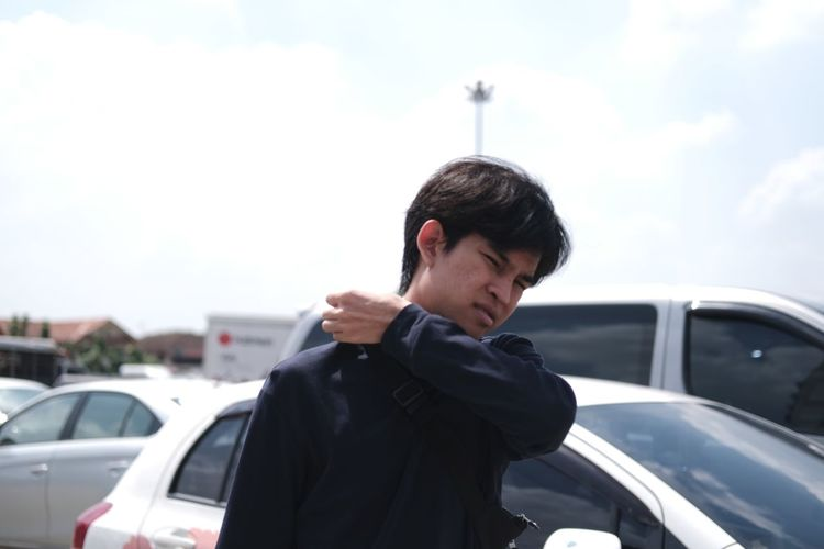 Young man looking away while standing on car against sky