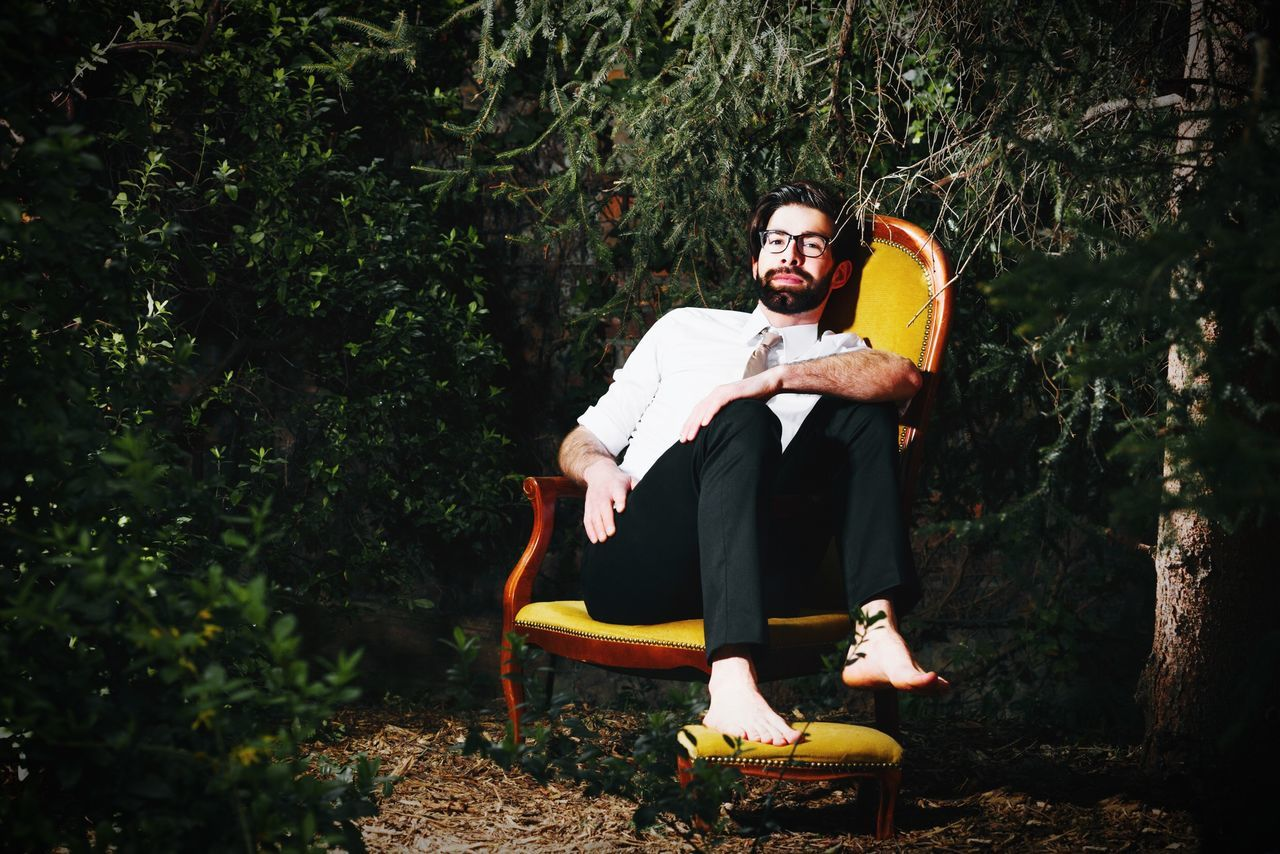 Portrait of young man sitting on chair by trees