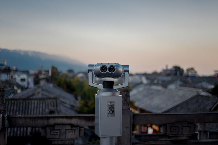 Close-up of coin-operated binoculars against buildings in city during sunset