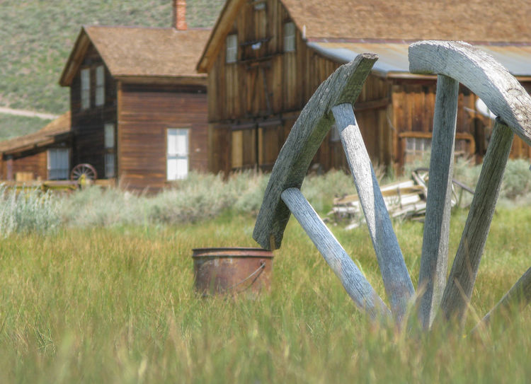 Agriculture Architecture Farm Farmhouse Ghost Town Ghost Town USA Grass Green Color House Rural Scene Tranquility Wagon Wheel Wagon Wheel At Abandoned House Western Wild West Summer Exploratorium