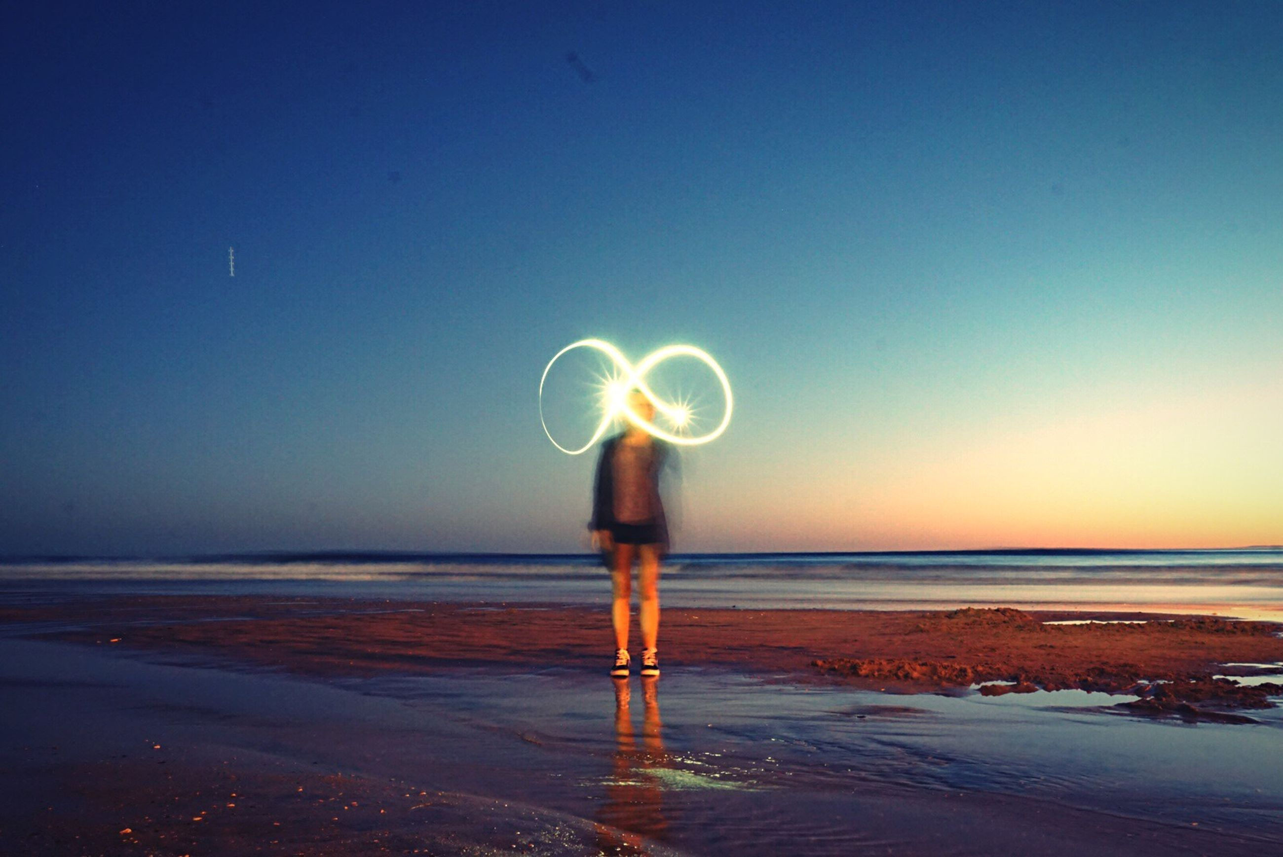 beach, illuminated, full length, water, pole, men, horizon over water, standing, clear sky, night, shore, street, coin-operated binoculars, tranquil scene, scenics, sea, carefree, outdoors, tranquility, blue, person, nature