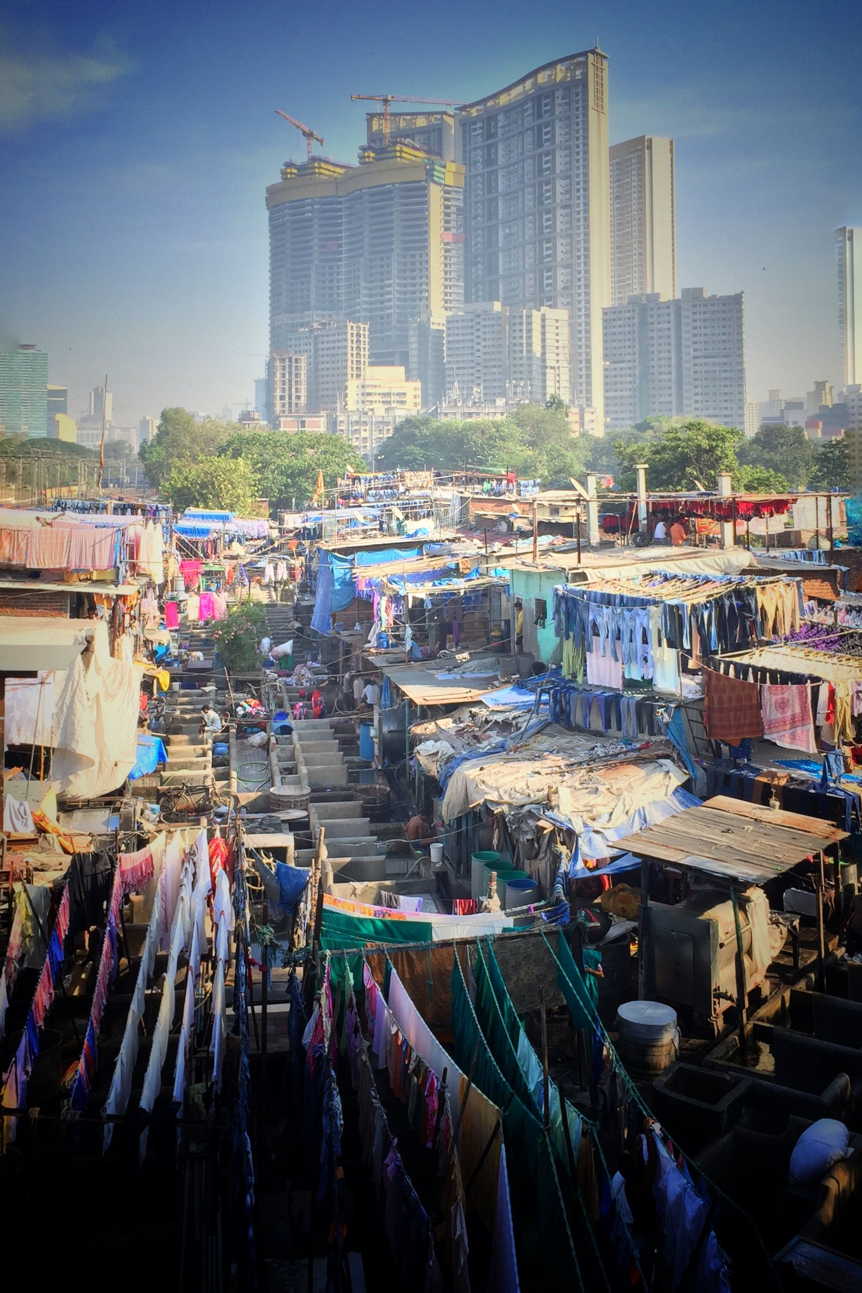 building exterior, city, architecture, built structure, city life, street, large group of people, cityscape, crowded, transportation, high angle view, sky, skyscraper, crowd, market, car, outdoors, abundance, day, mode of transport