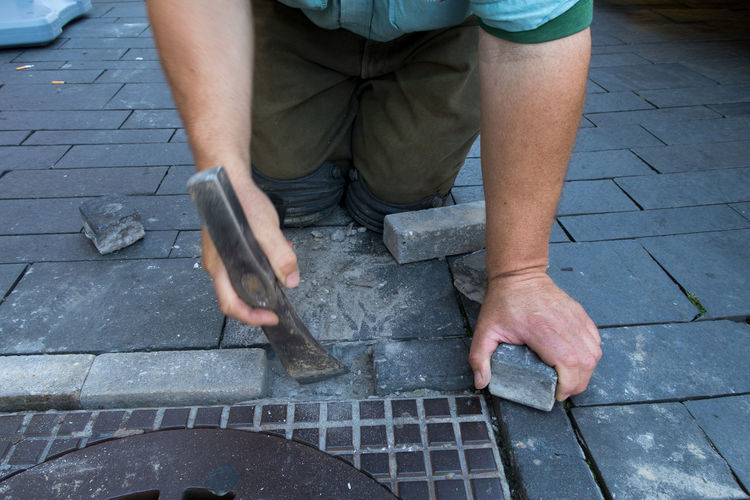 Midsection of construction worker working with axe by manhole on footpath
