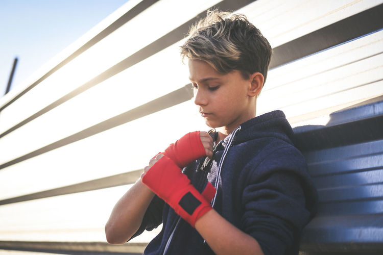 Boy wearing boxing strap while standing outdoors
