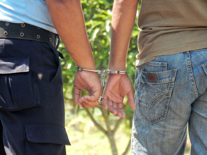 Close-Up Of Policeman And Criminal Handcuffed Together