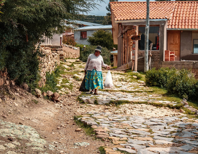 Exploring Isla del Sol and Copacabana, Bolivia. Copacabana Latin America Path Tradition Adult Adventure Architecture Building Building Exterior Built Structure Culture Discover  Explore Footpath House Nature Outdoors People Real People Residential District Senior Adult South America Travel Destinations Walking Women The Street Photographer - 2018 EyeEm Awards