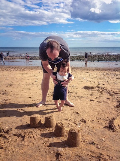 A father helps a toddler to learn to walk on Charmouth Beach. Beach Charmouth Child Dad Father Holiday Infant Learning To Walk Nature Outdoors Sand Sandcastles Sandy Sea Sky Son Toddler  Vacation Vacations