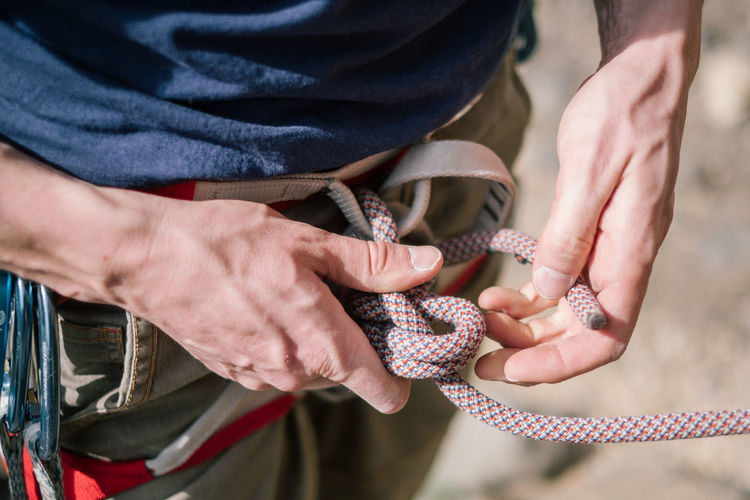 Midsection of male climber tying rope