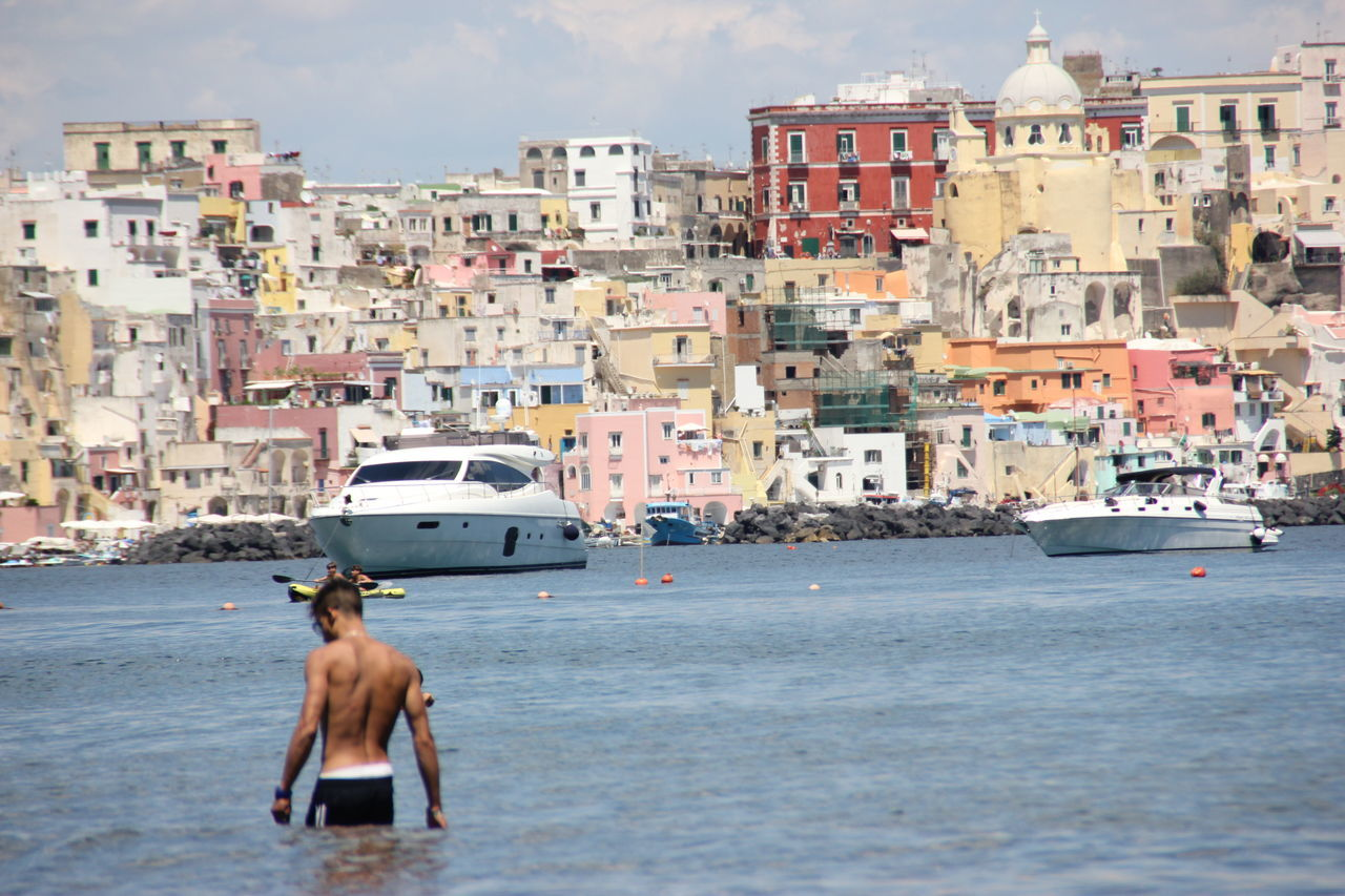 architecture, building exterior, sea, day, built structure, transportation, outdoors, shirtless, sky, real people, beach, vacations, nautical vessel, water, city, one person, nature, people