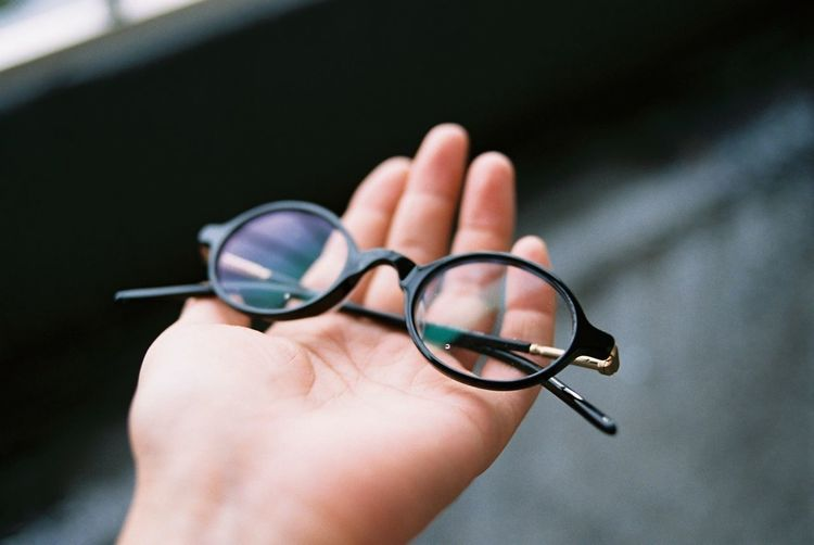 Cropped image of person holding eyeglasses
