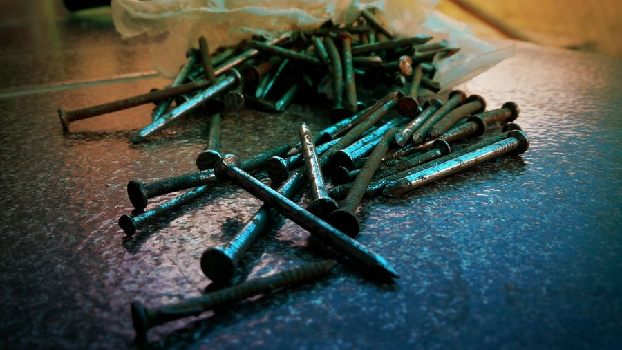 High angle view of rusty screws on table