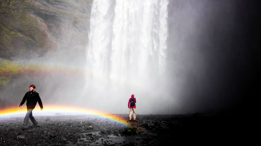 People by waterfall and rainbow in forest