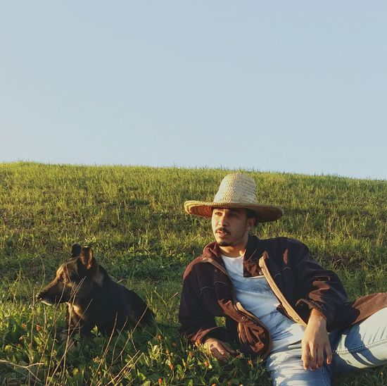 Young Man Looking Away While Relaxing With Dog On Grassy Field Against Sky