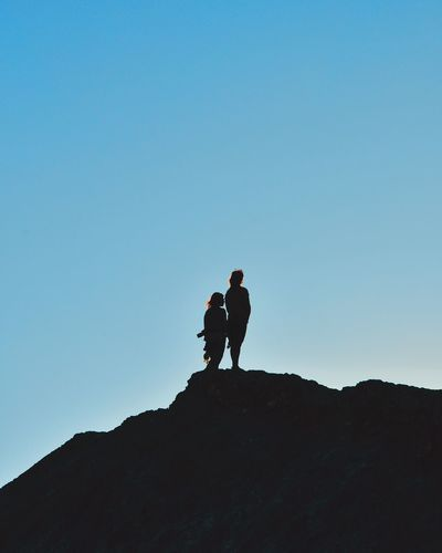 SILHOUETTE OF PEOPLE STANDING ON MOUNTAIN AGAINST BLUE SKY