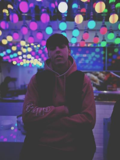 Portrait of young man standing against illuminated lights at nightclub