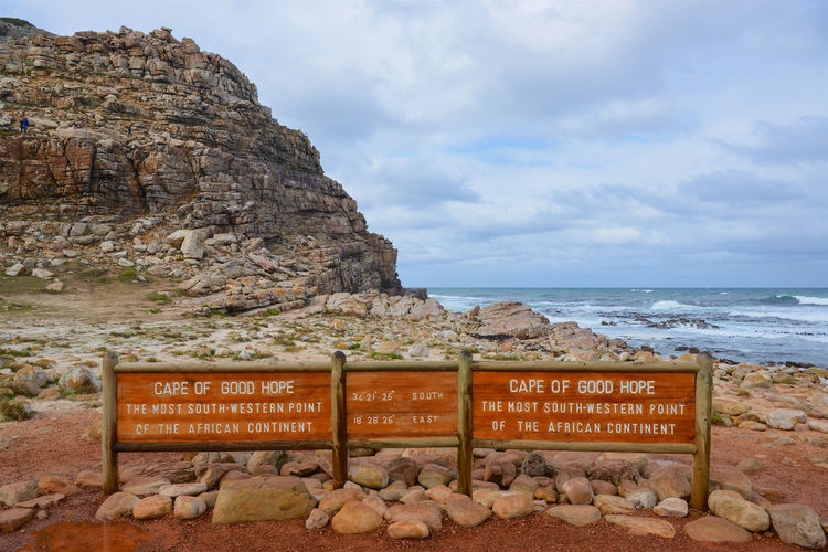 Information sign on rock by sea against sky