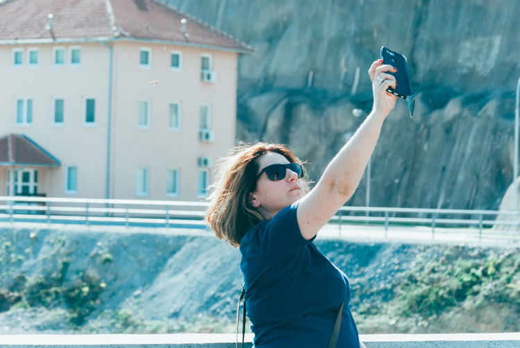 Woman wearing sunglasses taking selfie while standing outdoors
