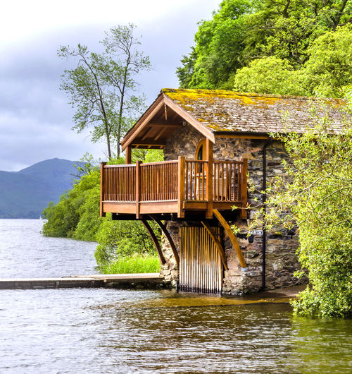 House by river against sky