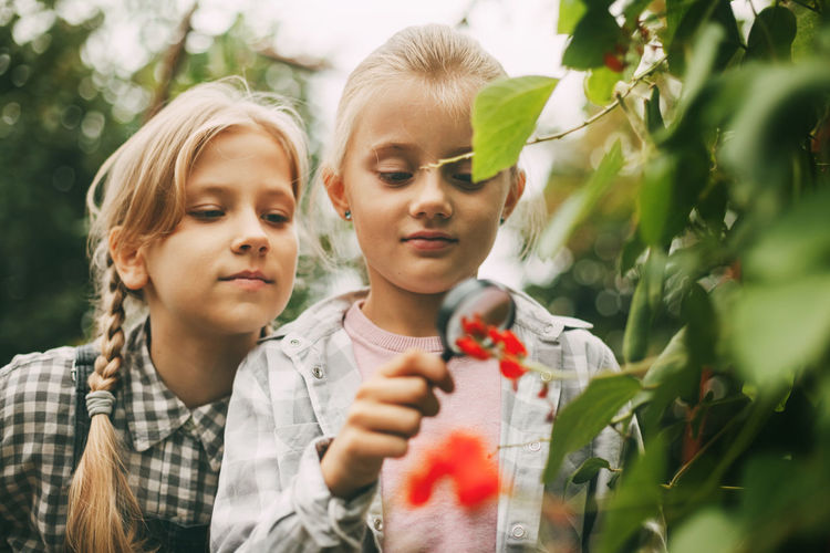Two beautiful little girls are exploring nature by writing their research on a tablet.