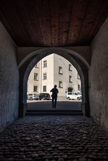 Man walking through arched gate