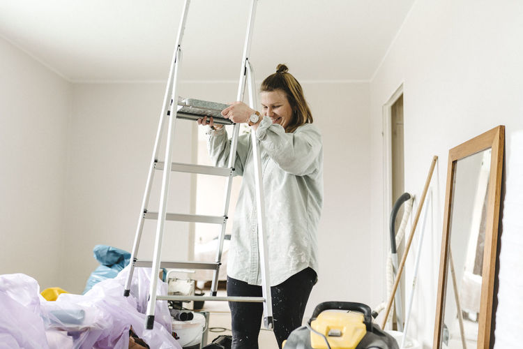 Woman looking down while standing on ceiling at home