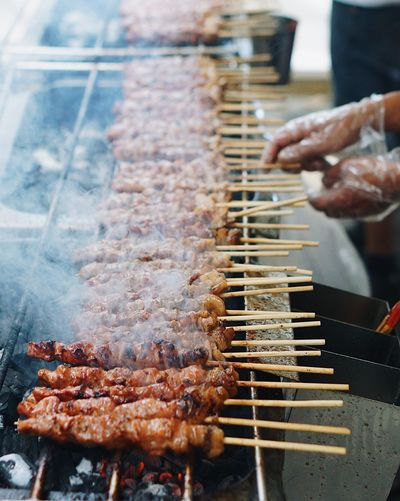Close-up of man roasting meat on barbecue grill